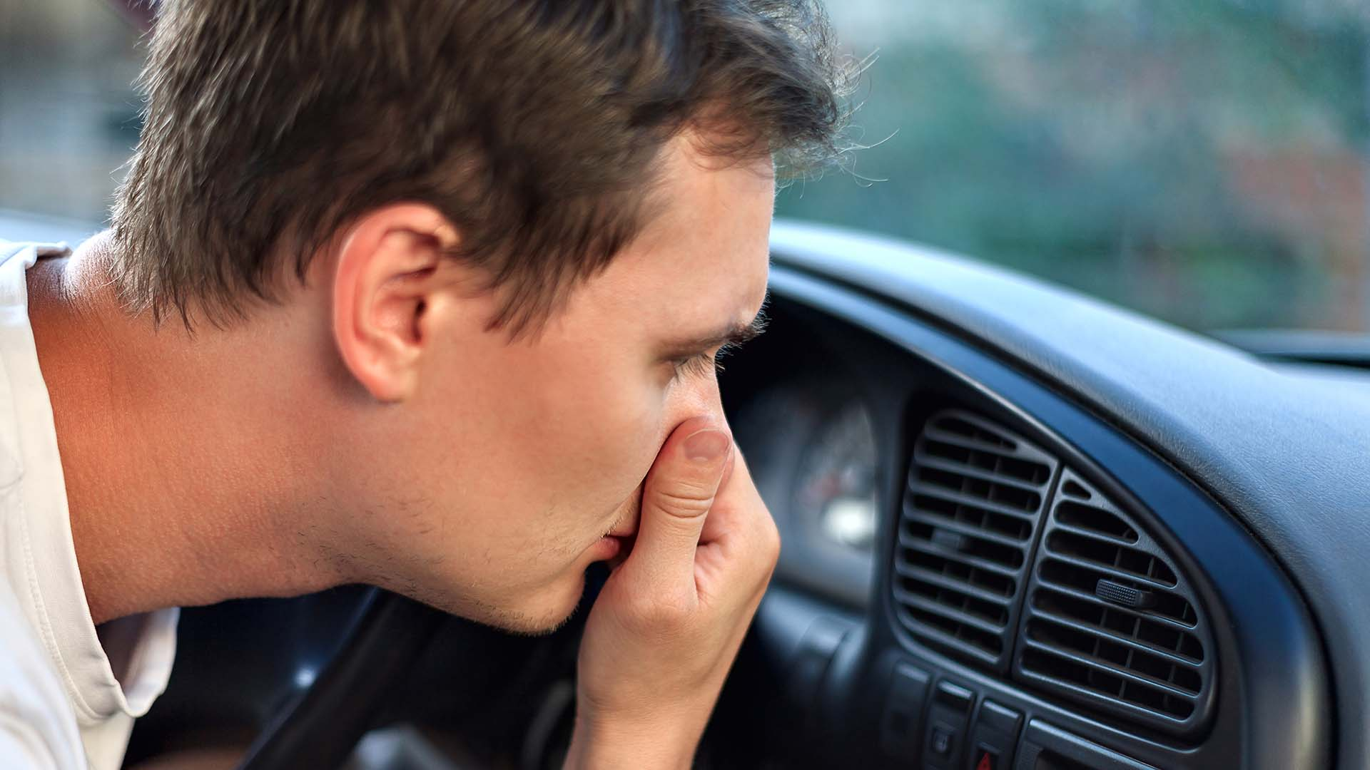 Man noticing a bad smell coming from car AC vents
