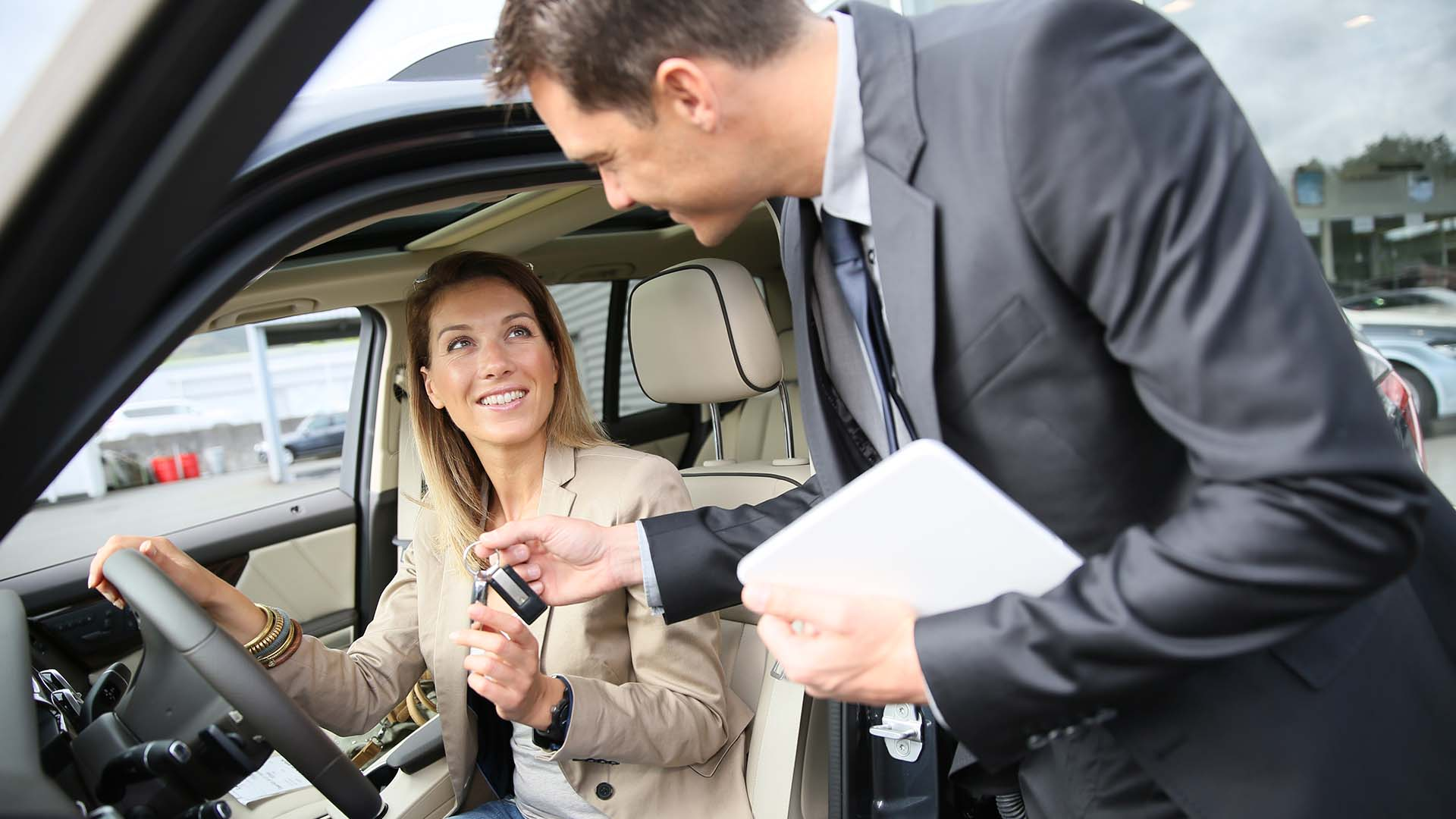woman receiving cars to a new car at the dealership