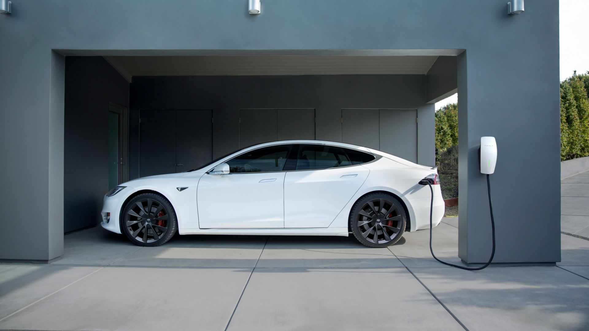 A white tesla being charged at home